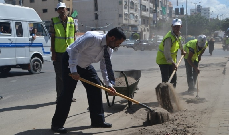 وزير الحكم المحلي في غزة محمد الفرا يشارك في تنظيف الشوارع خلال افتتاح مشروع تشغيل مئات عمال النظافة في غزة صباح اليوم